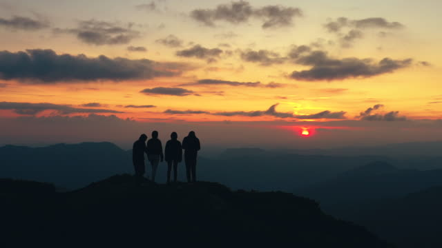 The four people standing on a mountain with the beautiful sunset