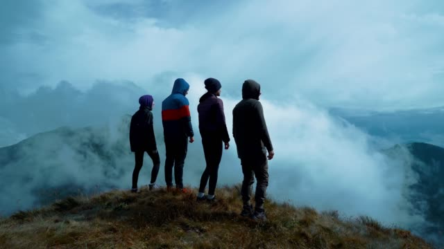 the four people standing on a picturesque mountain - пик стоковые видео и кадры b-roll