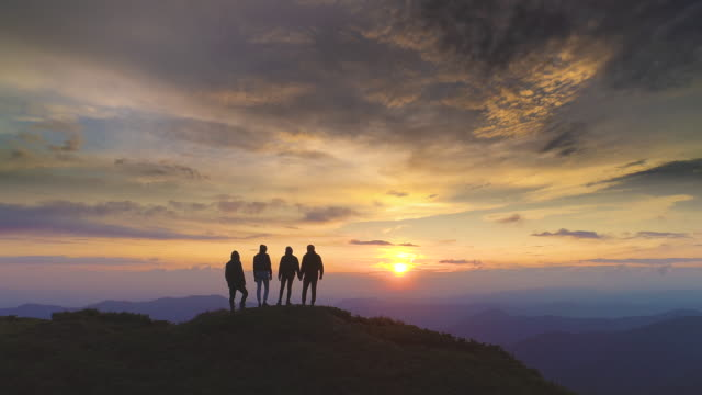 The four people standing on the mountain against the beautiful sunrise