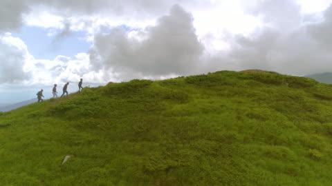 le quattro persone che camminano su per la montagna - collina video stock e b–roll