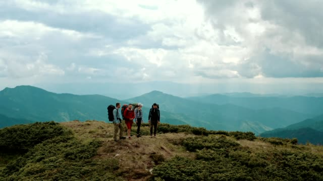The four people with backpacks standing on a mountain