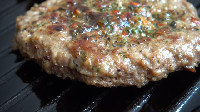 The fried cutlet for hamburger rotates on the grill pan. video