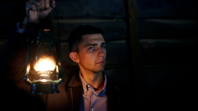 The frightened man in a suit standing in a dark room. Covers himself around a kerosene lamp video