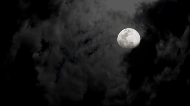 The full moon In the dark sky and the black clouds at night Moving up fast.