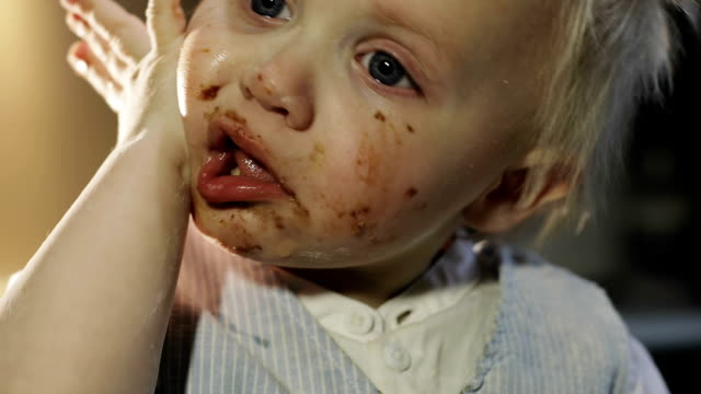 the funny boy smears his face in chocolate. - chef triste video stock e b–roll