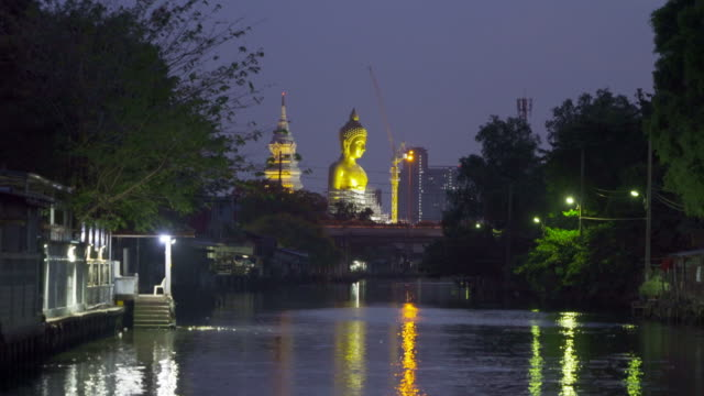 The Giant Golden Buddha in Wat Paknam Phasi Charoen Temple in Phasi Charoen district with boat on Chao Phraya River at night, Bangkok urban city, Thailand.