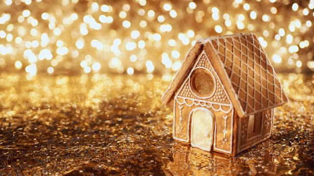 das lebkuchenhaus steht auf einer goldenen oberfläche und highlights werden auf das dach geworfen - lebkuchenhaus stock-videos und b-roll-filmmaterial