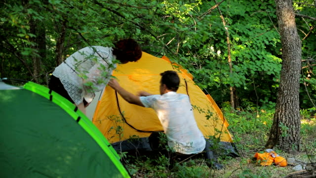 The girl and the man set the tent in the deciduous forest video