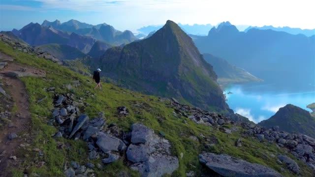 vídeos de stock e filmes b-roll de the girl comes down from the top of the mountain. - lofoten