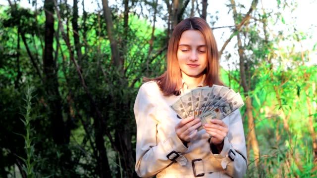 The girl counts cash dollars in the woods