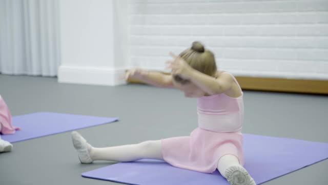 The girl does half split body bent during the ballet class in beautiful studio video