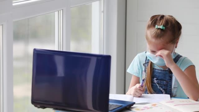 這個女孩做在線課程,做作業,看著窗外。互聯網學校,遠程學習,檢疫。一個無聊的小女孩在筆記本上寫字,看著一台筆記型電腦。 - back to school 個影片檔及 b 捲影像