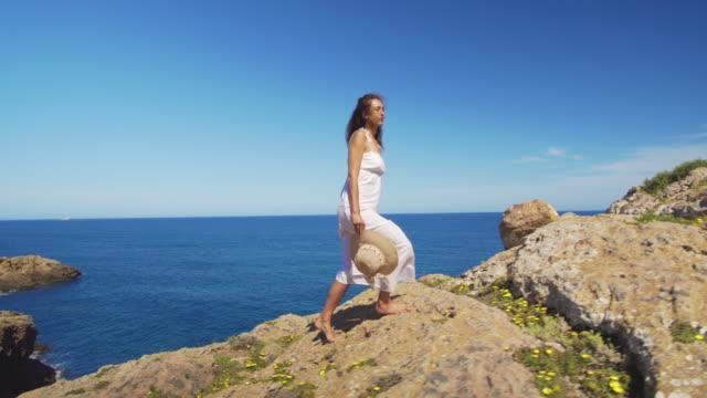 Het meisje gaat de klif op blote voeten tegen de blauwe zee video