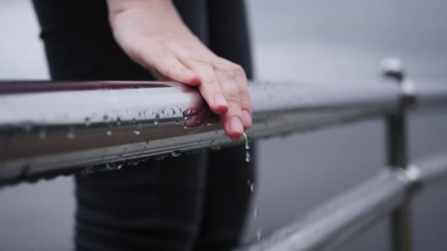 The girl holds her hand on the wet railings, drops flow down her thin fingers. video