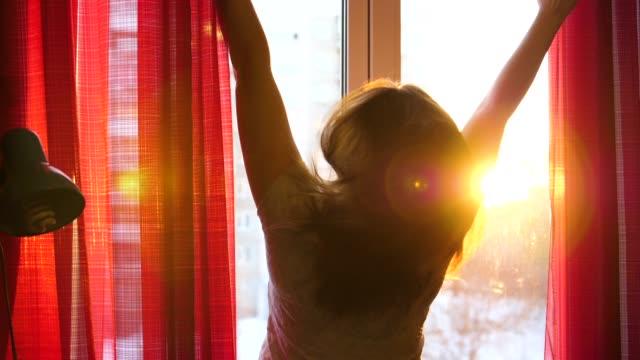 La jeune fille dans le debout tôt le matin à la fenêtre, ouvre les rideaux. Les rayons du soleil traversent le verre et illuminent la chambre avec la lumière du matin. - Vidéo