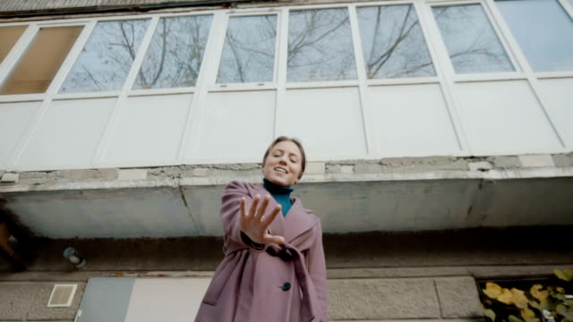 vídeos de stock e filmes b-roll de the girl in the lilac coat stands against the background of the old building and held out her hand. hand in focus. on hand ring. the frame moves away from the girl. slow motion. - puxar cabelos