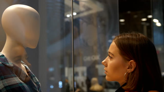 the girl in the store looks at the head of the mannequin her face is reflected in the window fashion look - modella negozio video stock e b–roll