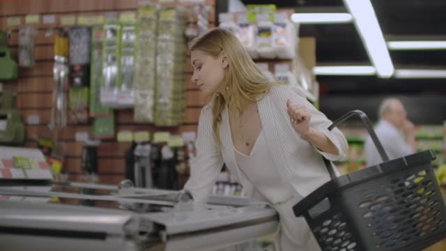 das mädchen im supermarkt nimmt aus dem kühlschrank tiefkühlkost liest die zusammensetzung des produkts und legt es in den korb. - gefrierkost stock-videos und b-roll-filmmaterial