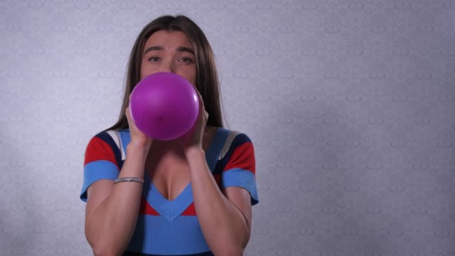 vídeos de stock e filmes b-roll de the girl inflates a purple balloon, takes in hand and releases, the ball is blown away and flies away. 4k slow mo - mulher balões