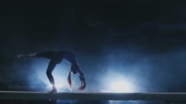 the girl is a professional athlete performs gymnastic acrobatic trick on a beam in backlight and slow motion in sports gymnastic clothing. smoke and blue. jump and spin on the balance beam - agilità video stock e b–roll