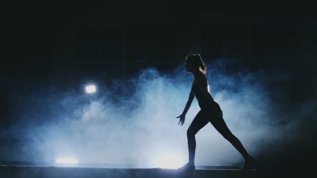 The girl is a professional athlete performs gymnastic acrobatic trick on a beam in backlight and slow motion in sports gymnastic clothing. Smoke and blue. Jump and spin on the balance beam