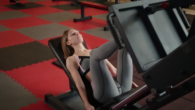 the girl is at the gym doing the leg press machine