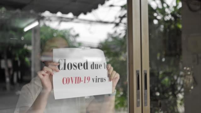 das mädchen schließt das ladenschild, store schließt wegen des ausbruchs der covid-19-viruspandemie - geschlossen allgemeine beschaffenheit stock-videos und b-roll-filmmaterial