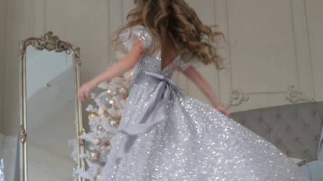the girl is dancing in a beautiful shiny dress. Christmas interior video