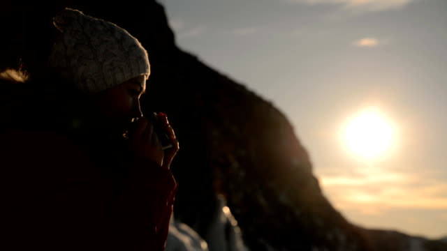 the girl is drinking tea at sunset. - bevanda calda video stock e b–roll