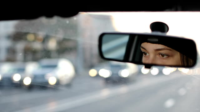 The girl is driving a car. Reflection of female eyes in the car rear view mirror. video