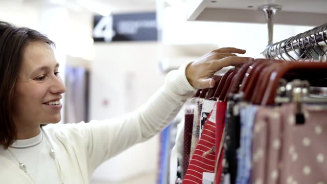 The girl is enthralled with different samples of color printed fabrics on the hangers and chooses one variant. Textile store. Side view The girl is enthralled with different samples of color printed fabrics on the hangers and chooses one variant. Textile store. Side view. fabric swatch stock videos & royalty-free footage