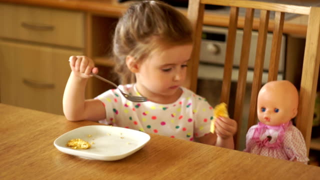 The girl is feeding the doll in the kitchen. She takes the food with her hands and eats it herself. Mother's Game The girl is feeding the doll in the kitchen. She takes the food with her hands and eats it herself. Mother's Game. HD doll stock videos & royalty-free footage