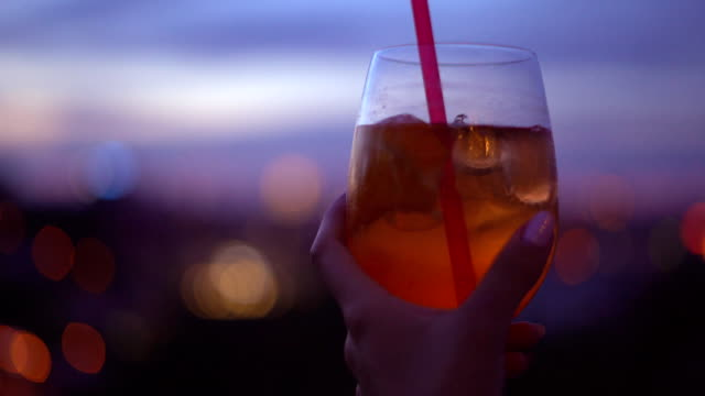 The girl is holding a glass of cocktail. Orange transparent drink with ice. Young river and a large wine glass against the sunset. A romantic evening. Soft focus video