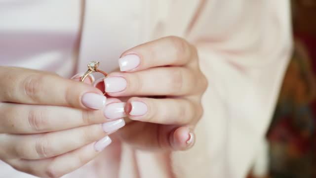 女の子は金の指輪にダイヤモンドを保持しています。 - 指輪点の映像素材/bロール