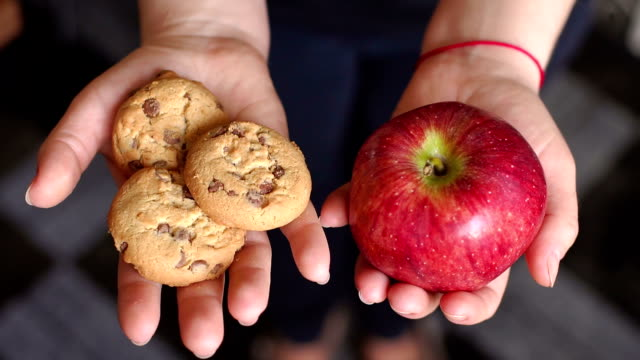 The girl is holding an apple and cookies, close-up The girl is holding an apple and cookies, close-up. Deciding what to choose. Hard choice between healthy and unhealthy food. Young female nutritionist holding apple and cookie, close-up. fat nutrient stock videos & royalty-free footage