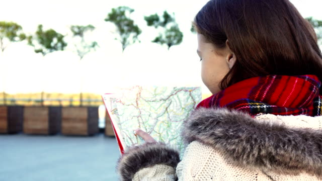 The girl is looking for the desired route on the map video