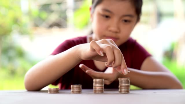 The girl is placing coins on the pile. Demonstrate savings in childhood. Show happy emotions.