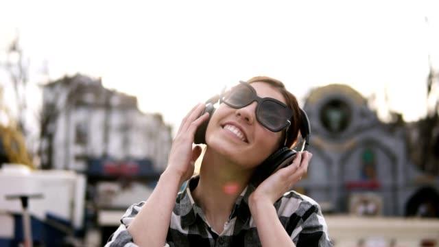 vidéos et rushes de la jeune fille est mise sur les écouteurs et commence à bouger avec les rythmes de la musique. lunettes de soleil. profitez-en. slow motion - casque audio