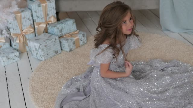 the girl is sitting in a beautiful shiny dress. Christmas interior video