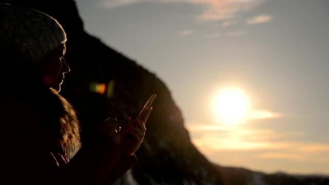 das mädchen nutzt das smartphone bei sonnenuntergang. - freizeitaktivität im freien stock-videos und b-roll-filmmaterial