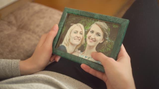 女の子は写真を見て、2人の女の子が描かれ、彼女の手をなでます。 - 家系図点の映像素材/bロール