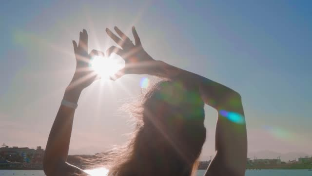 The girl make heart with her hands over sea background. Silhouette hand in heart shape with sunset inside. Vacation concept