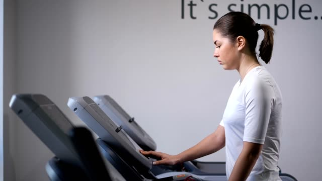 the girl on the treadmill. first comes, accelerates, starts to run. 4k slow mo - runner rehab gym video stock e b–roll