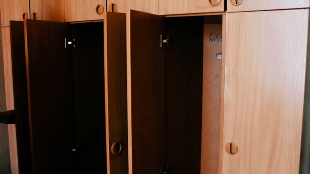 flickan öppnar och stänger en massa tomma skåp. tomma celler eller garderober i ett rum som öppnar och stänger - looking inside inside cabinet bildbanksvideor och videomaterial från bakom kulisserna