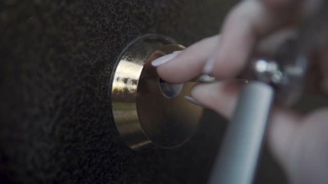 das mädchen öffnet das türschloss mit einem großen schlüssel. - hausschlüssel stock-videos und b-roll-filmmaterial