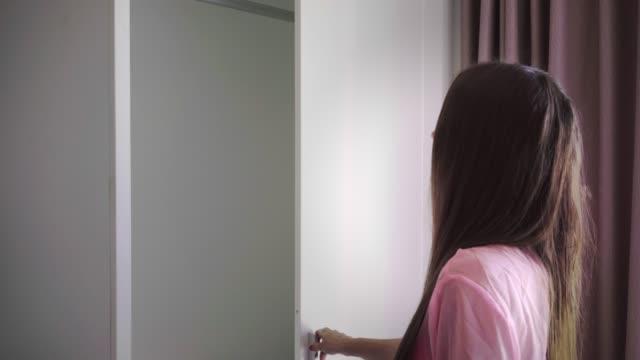 flickan öppnar garderoben, det finns inga kläder och en klänning i garderoben, honan är förvånad och ledsen. 4k - looking inside inside cabinet bildbanksvideor och videomaterial från bakom kulisserna