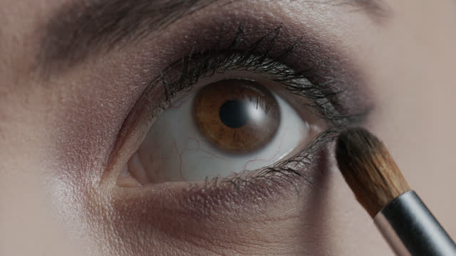 The girl paints the lower eyelid with dark eye shadow with a makeup brush. The girl paints the lower eyelid with dark eye shadow with a makeup brush. 4K 30fps ProRes 4444 eyeliner stock videos & royalty-free footage