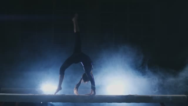the girl performs a trick on a log in backlight and slow motion in sports gymnastic clothing. smoke and blue. jump and spin on the balance beam - inarcare la schiena video stock e b–roll