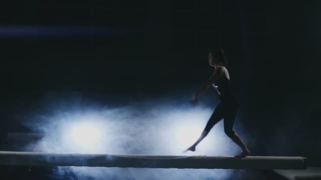 The girl performs a trick on a log in backlight and slow motion in sports gymnastic clothing. Smoke and blue. Jump and spin on the balance beam The girl performs a trick on a log in backlight and slow motion in sports gymnastic clothing. Smoke and blue. Jump and spin on the balance beam. landing touching down stock videos & royalty-free footage