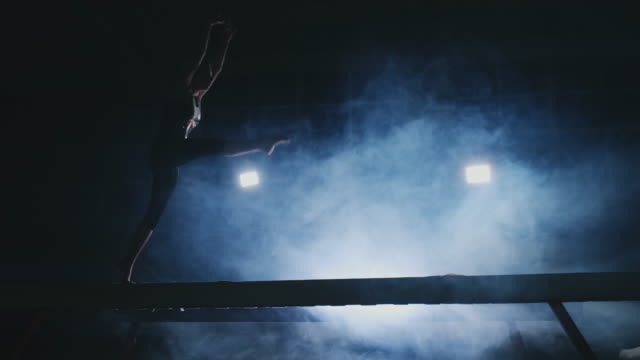 The girl performs a trick on a log in backlight and slow motion in sports gymnastic clothing. Smoke and blue. Jump and spin on the balance beam